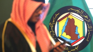 In this Dec. 5, 2017 file photo, a man looks at his mobile phone in front of the flag of the Gulf Cooperation Council, GCC, in Kuwait City. (AP Photo/Jon Gambrell, File)