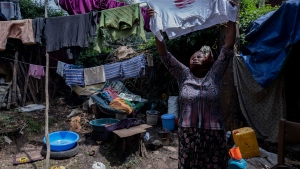 Mother of two Amsale Hailemariam, a domestic worker who lost work because of the coronavirus, hangs clothes after washing them outside her small tent in the capital Addis Ababa, Ethiopia on Friday, June 26, 2020. The virus arrived, and dreams faded for families, and entire countries. The world could see its first increase in extreme poverty in 22 years, further sharpening social inequities. (AP Photo/Mulugeta Ayene)