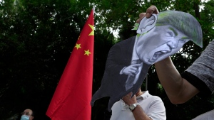 FILE - In this Aug. 8, 2020, file photo, pro-China supporters display a picture of U.S. President Donald Trump during a protest against the U.S. sanctions outside the U.S. Consulate in Hong Kong. China has announced Monday, Aug. 10, 2020, unspecified sanctions against 11 U.S. politicians and heads of organizations promoting democratic causes, including Senators Marco Rubio and Ted Cruz, who have already been singled out by Beijing. (AP Photo/Vincent Yu, File)