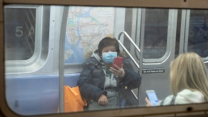In this March 19, 2020 file photo, a commuter wears a face mask while using their smart phone while riding the subway in New York. New York's mass transit agency wants Apple to come up with a better way for iPhone users to unlock their phones without taking off their masks, as it seeks to guard against the spread of the coronavirus in buses and subways.  (AP Photo/Mary Altaffer, File)