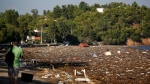 Debris covers the beach after a storm from the opposite island of Evia, as a man takes photographs in Chalkoutsi village, about 60 kilometres north of Athens, Monday, Aug. 10, 2020. (AP Photo/Thanassis Stavrakis)