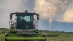 A funnel cloud is seen in the distance of a farmer's field near Virden, Man., in a Friday, Aug. 7, 2020, handout photo. THE CANADIAN PRESS/HO-Wyatt Hiebert,