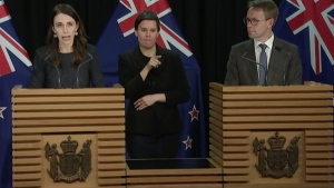 In this image from a video, New Zealand Prime Minister Jacinda Ardern, left, and Director-General of Health Ashley Bloomfield, right, attend a news conference in Wellington, New Zealand Tuesday, Aug. 11, 2020. Ardern says authorities have found four cases of the coronavirus in one Auckland household from an unknown source, the first cases of local transmission in the country in 102 days. (TVNZ via AP)