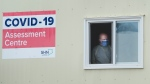A health care worker wearing protective gear looks out a window at a COVID-19 assessment centre at The Scarborough Hospital in Scarborough, Ont., on Friday, April 3, 2020. Health officials and the government has asks that people stay inside to help curb the spread of COVID-19. THE CANADIAN PRESS/Nathan Denette