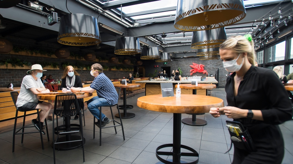 Patrons sit on the patio as waitress Paulina Pasierbek, right, walks by at Joey Sherway, part of the Joey Restaurant chain during the COVID-19 pandemic in Toronto on Wednesday, June 24, 2020. THE CANADIAN PRESS/Nathan Denette