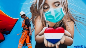A construction worker passes a mural by artist Casper Cruse, showing a woman with a face mask holding a heart in the colors of the dutch flag as a statement of support for those suffering from the effects of the coronavirus, in The Hague, Netherlands, Friday, April 24, 2020. (AP Photo/Peter Dejong)