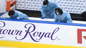 Cleaning crew staff disinfect the teams benches after the New York Islanders defeated the Florida Panthers during NHL Eastern Conference Stanley Cup playoff action in Toronto on Tuesday, August 4, 2020. Some of the stringent disinfection drills may seem over-the-top, especially as scientists concede that surface transmission is playing less of a role in spreading the novel coronavirus than initially thought, but most infectious disease experts say that doesn't mean we should ignore cleaning altogether.  THE CANADIAN PRESS/Nathan Denette