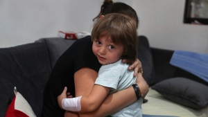 Hiba Achi hugs her son, three-year-old Abed Itani, at her house in Beirut, Lebanon, Tuesday, Aug. 11, 2020. Abed was playing with his Lego blocks when the huge blast ripped through Beirut, shattering the nearby glass doors. He had cuts on his tiny arms and feet, a head injury, and was taken to the emergency room, where he sat amid other bleeding people. (AP Photo/Bilal Hussein)