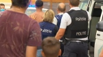 In image made from video provided by VTM, a man is detained by police, centre back, after a skirmish on the beach in Blankenberge, Belgium on Saturday, Aug. 8, 2020. It started as a Saturday trip to the coast, a chance to escape the heat wave that's settled over Belgium and forget coronavirus restrictions for a while. As the tide came in, the beach got crowded. Someone complained about the music being too loud. Things degenerated fast. Within minutes, dozens of people were battling it out on the sand, some throwing bottles and umbrellas at police. (VTM via AP)