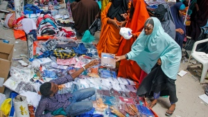 People shop in a street market in preparation for the Muslim holiday of Eid al-Fitr, which marks the end of the holy fasting month of Ramadan, in Mogadishu, Somalia Tuesday, May 19, 2020. (AP Photo/Farah Abdi Warsameh)