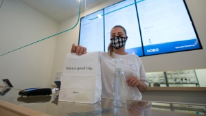 Employee Sophia Lovink shows off a bag of merchandise at the HOBO Cannabis Company during the COVID-19 pandemic in Toronto on Thursday, June 11, 2020. When hospitality business Donnelly Group rang in the new year, opening two Hobo Cannabis Company stores in March and April were top priorities. THE CANADIAN PRESS/Nathan Denette
