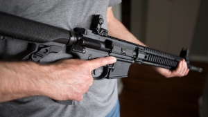 "A restricted gun licence holder holds a AR-15 at his home in Langley, B.C., on May 1, 2020. The federal government is turning to the private sector to design and run a massive buyback of newly prohibited firearms. Public Safety Canada has invited 15 consulting firms to come up with a ""range of options and approaches"" for the planned program to compensate gun owners. THE CANADIAN PRESS/Jonathan Hayward"