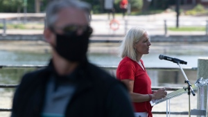 A member of the RCMP surveys the area as Infrastructure and Communities Minister Catherine McKenna speaks during an announcement along the Rideau canal, in Ottawa, Thursday, Aug. 13, 2020. THE CANADIAN PRESS/Adrian Wyld