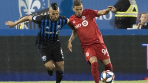Montreal Impact's Saphir Taider, left, challenges Toronto FC's Auro during second half MLS soccer action in Montreal on July 13, 2019. Canada's three MLS teams will continue their regular season north of the border, playing each other three times in the first phase of the league's revamped schedule. THE CANADIAN PRESS/Graham Hughes