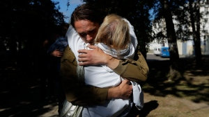 A couple hug after being released from a detention center where protesters were detained during a mass rally following the presidential election in Minsk, Belarus, Friday, Aug. 14, 2020. Nearly 7,000 people have been detained and hundreds injured in the clampdown on demonstrators protesting the official results that said Lukashenko won 80% of the vote and his top opposition challenger got only 10%. Police have broken up protests with stun grenades, tear gas, rubber bullets and severe beatings. (AP Photo/Sergei Grits)