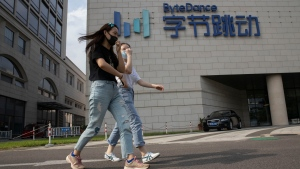 Women wearing masks to prevent the spread of the coronavirus chat as they pass by the ByteDance headquarters in Beijing, China on Friday, Aug. 7, 2020. (AP Photo/Ng Han Guan)