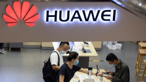 In this July 15, 2020 file photo, visitors wearing masks to curb the spread of the coronavirus look at the latest products at a Huawei store in Beijing. (AP Photo/Ng Han Guan, File)