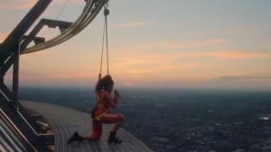 Singer Jessie Reyez kneels atop the CN Tower to sing 'O Canada.' (@Raptors /Twitter)