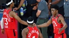 Toronto Raptors forward guard Malcolm Miller, left,, guard Kyle Lowry (1), and Stanley Johnson (5) celebrate their win over the Brooklyn Nets in Game 3 of an NBA basketball first-round playoff series, Friday, Aug. 21, 2020, in Lake Buena Vista, Fla. (Kim Klement/Pool Photo via AP)