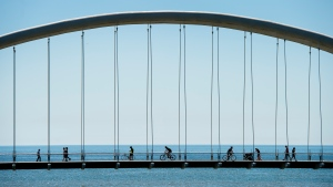 People get exercise in the warm weather as they cross the Humber Bay bridge over looking Lake Ontario during the COVID-19 pandemic in Toronto on Tuesday, June 9, 2020. THE CANADIAN PRESS/Nathan Denette