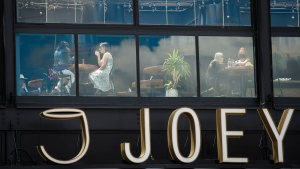Patrons are seen though a window sitting on the patio at Joey Sherway, part of the Joey Restaurant chain during the COVID-19 pandemic in Toronto on Wednesday, June 24, 2020. THE CANADIAN PRESS/Nathan Denette
