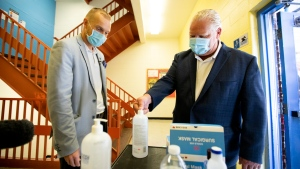Ontario Premier Doug Ford, right, uses hand sanitizer as he gets a tour of Kensington Community School from principal Dan Fisher to see the safety measures implemented as students return to school amidst the COVID-19 pandemic on Tuesday, September 1, 2020. THE CANADIAN PRESS/Carlos Osorio