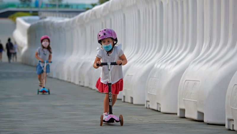 Kids wearing masks to protect against the coronavirus, play beside the water-filled barriers outside the Hong Kong Government Office in Hong Kong, Thursday, Aug. 20, 2020. (AP Photo/Kin Cheung)
