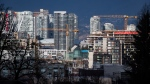 Construction cranes tower above condos under construction near southeast False Creek in Vancouver, on Sunday February 9, 2020. THE CANADIAN PRESS/Darryl Dyck