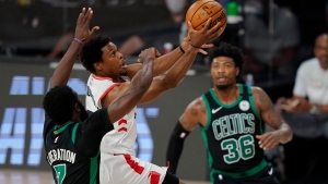 Toronto Raptors' Kyle Lowry, center, goes to the basket between Boston Celtics' Jaylen Brown (7) and Marcus Smart (36) in the first half of an NBA conference semifinal playoff basketball game Tuesday, Sept. 1, 2020, in Lake Buena Vista, Fla. (AP Photo/Mark J. Terrill)