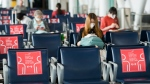 """People wearing mandatory masks wait at their gate using physical distancing at Toronto's Pearson International Airport for a """"Healthy Airport"""" during the COVID-19 pandemic in Toronto on Tuesday, June 23, 2020. THE CANADIAN PRESS/Nathan Denette"""