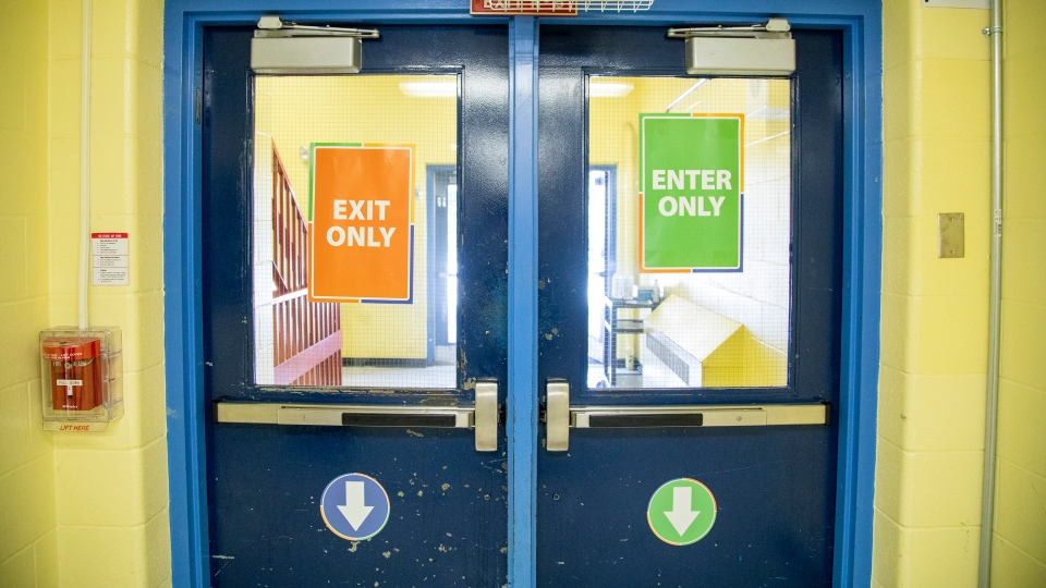 Signs helping direct the flow of student traffic are seen at Kensington Community School amidst the COVID-19 pandemic on Tuesday, September 1, 2020. THE CANADIAN PRESS/Carlos Osorio