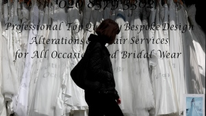 A woman walks past a Wedding dress shop in London, Tuesday, June 9, 2020, where bride dresses pile unused in the shop window. (AP Photo/Frank Augstein)