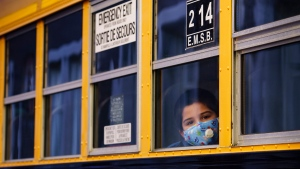 A student peers through the window of a school bus as he arrives at the Bancroft Elementary School in Montreal, on August 31, 2020. School bus cancellations are piling up in Ontario as transportation providers cite COVID-19 fears that have worsened a shortage of bus drivers in the industry. Twelve bus routes were cancelled in both the Grey-Bruce and Thunder Bay regions as of Wednesday, with providers saying health concerns from the pandemic are keeping drivers off the job. THE CANADIAN PRESS/Paul Chiasson