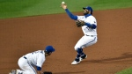 Toronto Blue Jays shortstop Jonathan Villar, right, reaches for a grounder by New York Yankees' Gleyber Torres that deflected off third baseman Joe Panik, left, during the ninth inning of a baseball game in Buffalo, N.Y., Wednesday, Sept. 9, 2020. Torres was out at first. Aaron Hicks scored from third. (AP Photo/Adrian Kraus)