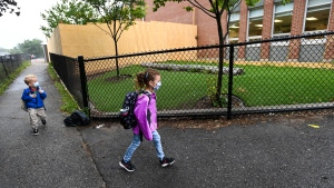 Six-year-old Peyton Denette, right, and her five-year-old brother Maverick Denette return to school for their first day at St. Thomas More Elementary School in Mississauga, Ont., on Wednesday, September 9, 2020. THE CANADIAN PRESS/Nathan Denette