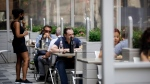 A waiter talks with patrons at a patio in Yorkville in Toronto, on Friday, June 26, 2020. THE CANADIAN PRESS/Cole Burston