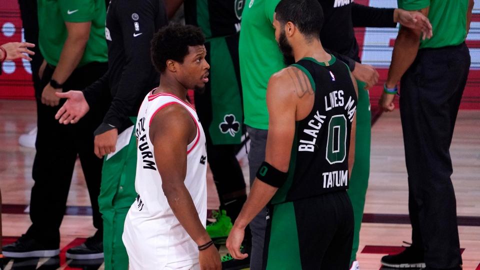 Toronto Raptors' Kyle Lowry, left, talks with Boston Celtics' Jayson Tatum after an NBA conference semifinal playoff basketball game Friday, Sept. 11, 2020, in Lake Buena Vista, Fla. The Celtics won 92-87. (AP Photo/Mark J. Terrill)