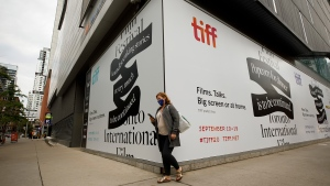 A person walks past the Toronto International Film Festival's TIFF Bell Lightbox theatre on King St., in Toronto, ahead of the festival's opening night, Thursday, Sept. 10, 2020. Netflix and the Toronto International Film Festival have been an inseparable power couple for years, mastering the ways to get moviegoers talking, but during the pandemic their storied Hollywood relationship is on a break. THE CANADIAN PRESS/Cole Burston