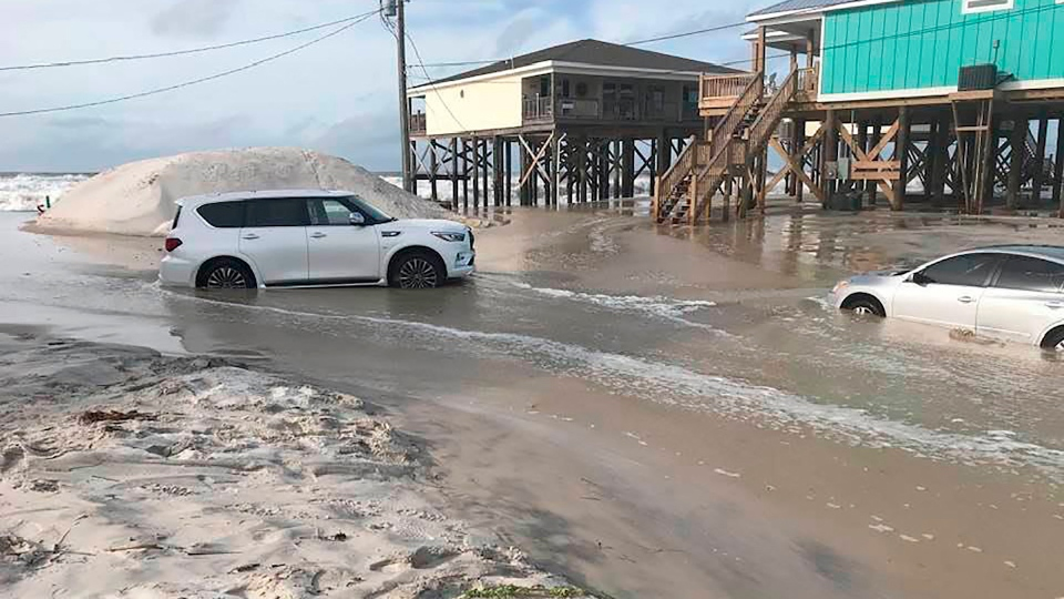This photo provided by Dauphin Island Mayor Jeff Collier shows cars stranded in the sand, as flooding continues in Tonty Court on Dauphin Island, Ala., Monday, Sept 14, 2020, as Sally closes in on the Gulf Coast. (Jeff Collier via AP)