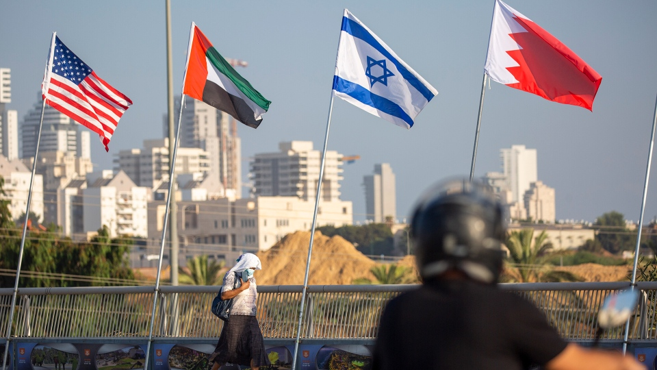 """A woman wearing a face mask against the coronavirus pandemic walks past American, United Arab Emirates, Israel and Bahraini flags at the Peace Bridge in Netanya, Israel, Monday, Sept. 14, 2020. For the first time in more than a quarter-century, a U.S. president will host a signing ceremony between Israelis and Arabs at the White House, billing it as an """"historic breakthrough"""" in a region long known for its stubborn conflicts. (AP Photo/Ariel Schalit)"""