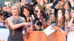 """In this file photo, actor Kate Winslet signs autographs for fans as she arrives on the red carpet at the gala for the film """"The Dressmaker,"""" at the 2015 Toronto International Film Festival on Monday, Sept. 14, 2015. THE CANADIAN PRESS/Frank Gunn"""