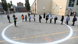 Children wait in a physical distancing circle at Portage Trail Community School which is part of the Toronto District School Board (TDSB) during the COVID-19 pandemic in Toronto on Tuesday, September 15, 2020. THE CANADIAN PRESS/Nathan Denette