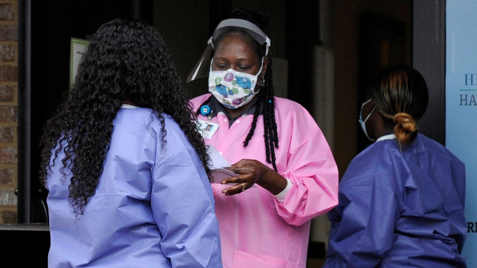 """FILE- In this May 27, 2020, photo, health care workers talk outside a Lowndes County coronavirus testing site in Hayneville, Ala. Experts say Lowndes County and nearby poor, mostly black counties in rural Alabama are now facing a """"perfect storm"""" as infections tick up: a lack of access to medical care combined with poverty and the attendant health problems that can worsen the outcomes for those who become sick. (AP Photo/Jay Reeves)"""