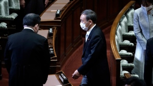 Japan's new Prime Minister Yoshihide Suga, right, leaving after an extraordinary session at the upper house of parliament Thursday, Sept. 17, 2020, in Tokyo. Suga started his first full day in office Thursday, with a resolve to push for reforms for the people, and he said he is already taking a crack at it. (AP Photo/Eugene Hoshiko)