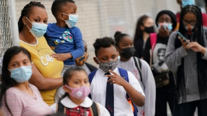 In this Sept. 9, 2020, file photo, students wear protective masks as they arrive for classes at the Immaculate Conception School while observing COVID-19 prevention protocols in The Bronx borough of New York. (AP Photo/John Minchillo)