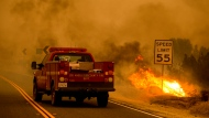 A Los Angeles County Fire Department truck drives through smoke, next to a small area burning in the Bobcat Fire in Juniper Hills, Calif., Friday, Sept. 18, 2020. (AP Photo/Ringo H.W. Chiu)