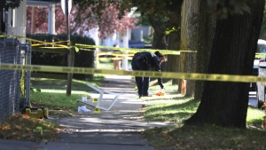 A Rochester police technician picks up some items as evidence near the home where a fatal house party took place, Saturday, Sept. 19, 2020, in Rochester, N.Y. A pair of sneaker are scattered around a tipped chair. Police in Rochester, New York, say several people died and others were wounded by gunfire at a backyard party early Saturday. (Tina MacIntyre-Yee/Democrat & Chronicle via AP)