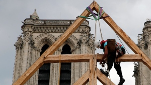 Charles, one of the carpenters puts the skills of their Medieval colleagues on show on the plaza in front of Notre Dame Cathedral in Paris, France, Saturday, Sept. 19, 2020, the day honoring European heritage, by reproducing for the public a section of the elaborate carpentry used when the edifice was built. The elaborate wooden beams went up in flames in a devastating April fire that also toppled the spire of the cathedral, now being renovated. (AP Photo/Francois Mori)