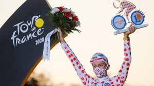 Tour de France winner Slovenia's Tadej Pogacar, who also won the best climber's dotted jersey, celebrates on the podium after the twenty-first and last stage of the Tour de France cycling race over 122 kilometers (75.8 miles), from Mantes-la-Jolie to Paris, France, Sunday, Sept. 20, 2020. (AP Photo/Christophe Ena)