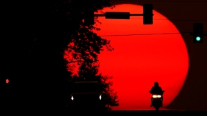A motorcyclist is silhouetted against the setting sun, Sunday, Sept. 20, 2020, in Shawnee, Kan. Sunsets have been more vibrant than normal recently as smoke from western wildfires drifts across the United States. (AP Photo/Charlie Riedel)
